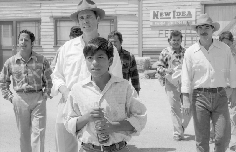 Marcos (José Alcala) approaches the carpenter&#039;s trailer, urged on by the older men. <br /><br /> Photograph by Carlos Rene Perez. Severo Perez Papers, Wittliff Collections, Texas State University.