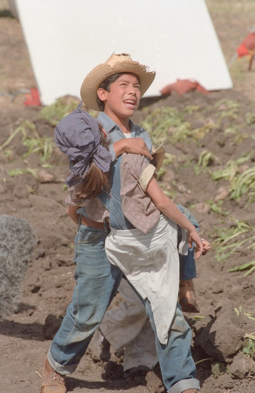 Marcos (José Alcala) carries his sister after she collapses in a sugar beet field.&lt;br /&gt;<br />