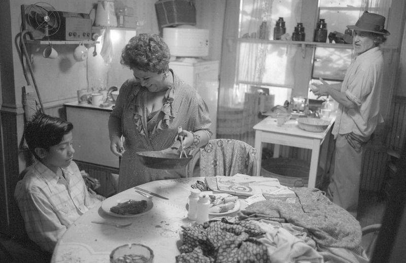 Dona Rosa (Lupe Ontiveros) offers Marcos dinner.  <br /><br /> Photograph by Carlos Rene Perez. Severo Perez Papers, Wittliff Collections, Texas State University.