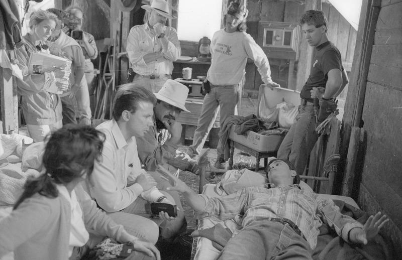 Filming the scene in the chicken coop as Joaquin (Marco Rodriguez) recovering from heat stroke suffered in the fields as the contractor (Daniel Haro) looks on. <br /><br /> Photograph by Carlos Rene Perez. Severo Perez Papers, Wittliff Collections, Texas State University.