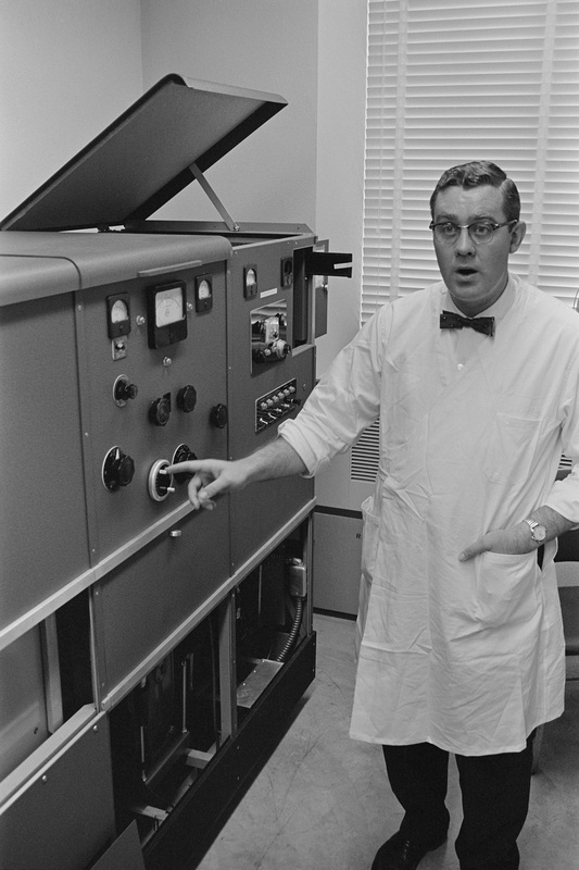 Chemistry professor Dr. Charles Willms, standing by a chromatograph.